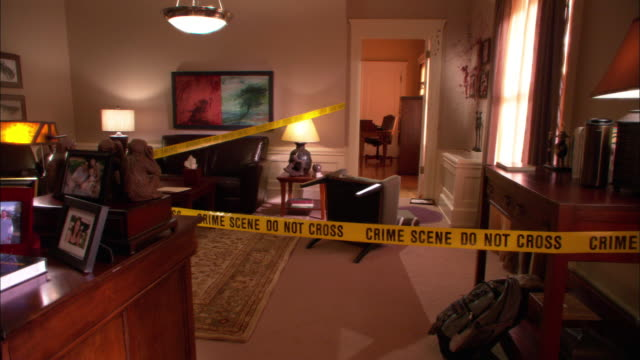 medium angle of office or home taped off with police tape. could be crime scene. chair knocked over in bg beside blood stained carpet. gore and blood on wall. could be living room. - gore stock videos & royalty-free footage
