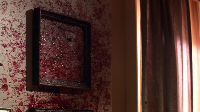 close angle of diploma in picture frame hanging on wall. could be doctor's office or dentists office. bullet shatters frame and blood and gore cover wall. frame flies off wall. could be murder. - fensterrahmen stock-videos und b-roll-filmmaterial