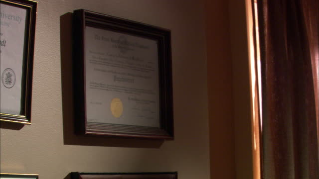 stockvideo's en b-roll-footage met close angle of diploma in picture frame hanging on wall. could be doctor's office or dentists office. - diploma