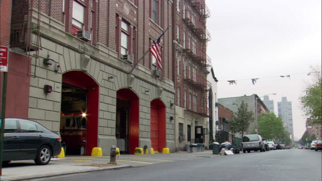 medium angle of grey stone fire station or fire house with three red garage doors. lights flashing through open garage doors. fire truck or fire engines leave garage turning left onto city street. - fire station stock videos & royalty-free footage