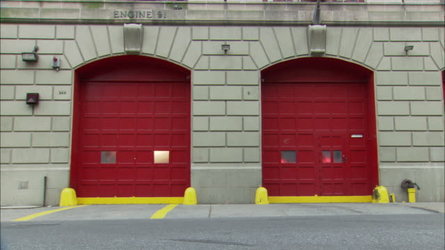 vídeos y material grabado en eventos de stock de medium angle of two red garages of stone fire station. lights flashing through windows of garages. garage doors open and fire chief suv and two fire engines or fire trucks drive out of station turning left onto city street - parque de bomberos