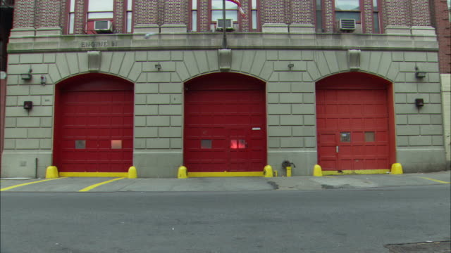 medium angle of two red garages of stone fire station. lights flashing through windows of garages. garage doors open and fire chief suv and two fire engines or fire trucks drive out of station turning left onto city street - feuerwache stock-videos und b-roll-filmmaterial