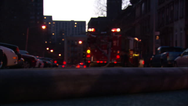 medium angle of a fire engine parked on the side of the street in harlem with a large fire hose in the fg. - fire engine stock videos & royalty-free footage