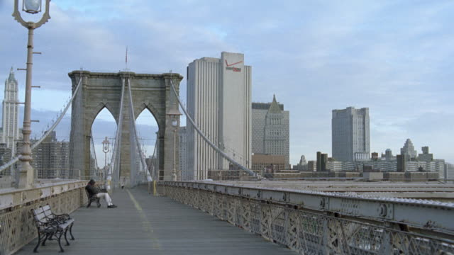 wide angle of new york city skyline. brooklyn bridge in fg. camera from pedestrian path facing directly down bridge. verizon logo on building in bg. other skyscrapers and high rise buildings in bg. - brooklyn bridge stock videos & royalty-free footage