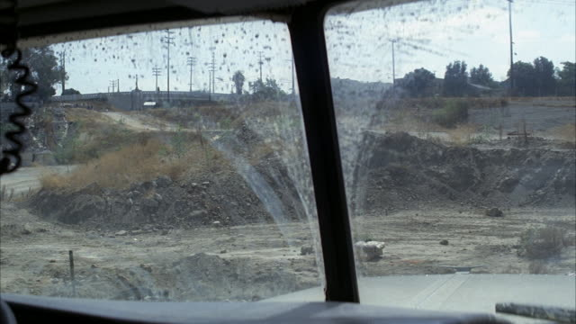 medium angle from inside garbage or cement truck of stone quarry. dirt on windshield. explosion goes off in front of truck. dust, debris, and rubble fly into air. - windschutzscheibe stock-videos und b-roll-filmmaterial