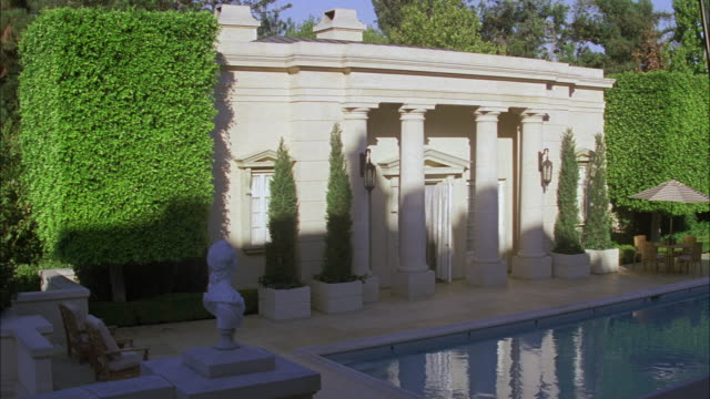 wide angle of fleur de lys mansion. stone building, upper class house. swimming pool in backyard. los angeles area. - fleur de lys stock videos & royalty-free footage