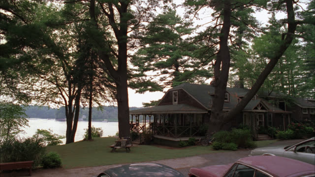 wide angle of two story cabin or house on lake chebacco. pine trees. cars parked in fg. could be vacation house. - 小屋点の映像素材/bロール