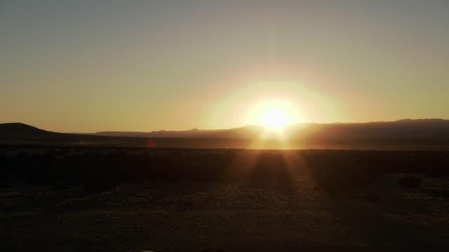 vídeos de stock e filmes b-roll de wide angle of sunset behind desert, prairie, or grassland landscape. - planície