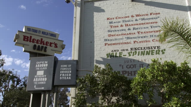 "up angle of ""bleeker's cafe"" restaurant sign on sony pictures studio lot. movie studios. two story painted brick building. los angeles area. - culver city stock videos & royalty-free footage"