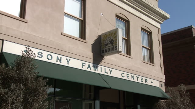 """vídeos y material grabado en eventos de stock de medium angle of """"sony family center"""" sign above awning. neon sign for """"radios"""". electronics store or storefront on main street. two-story building. sony pictures studio lot. los angeles area. - street name sign"""
