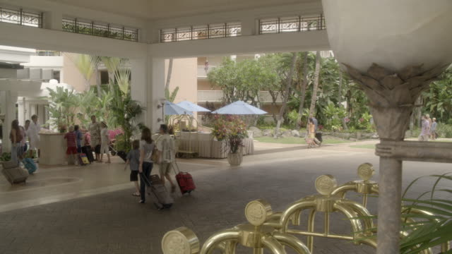 wide angle of upper class resort or hotel with tropical plants. guests visible and dollies for moving luggage. umbrellas. could be lobby. - lobby stock videos & royalty-free footage