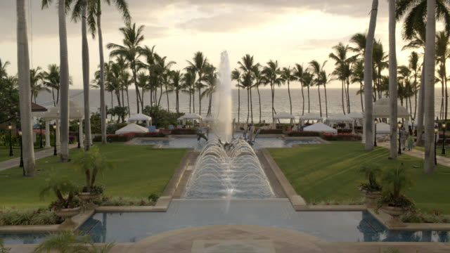 high angle down of fountain with dolphin sculptures and reflecting pool at grand wailea hotel and resort in hawaii. cabanas, palm trees, and ocean visible in bg. guests walk around fountain. upper class. - cetacea stock videos & royalty-free footage