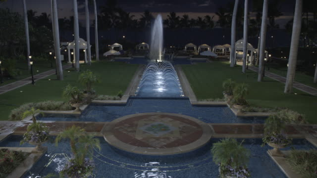high angle down of fountain and reflecting pool at grand wailea hotel and resort. upper class. dolphin sculpture in fountain in  bg. ocean and palm trees in bg. cabanas visible. plants and flowers visible. - cetacea stock videos & royalty-free footage