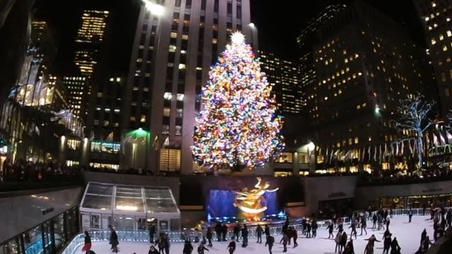 vídeos de stock, filmes e b-roll de christmas at rockefeller center tree prometheus skaters pan from tree to skaters and back - centro rockefeller
