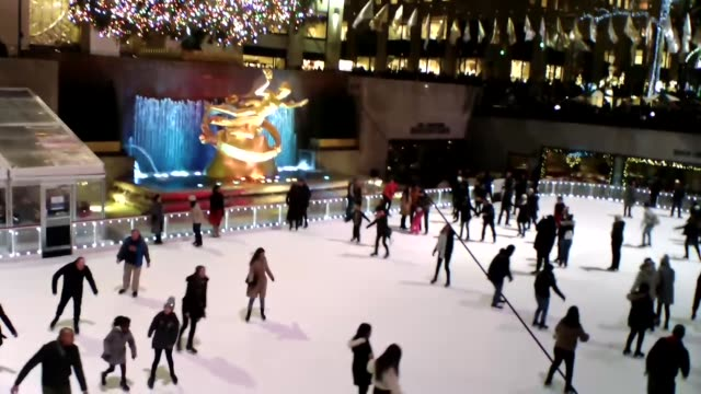 christmas at rockefeller center tree prometheus skaters pan from tree to skaters and back - global village stock videos & royalty-free footage