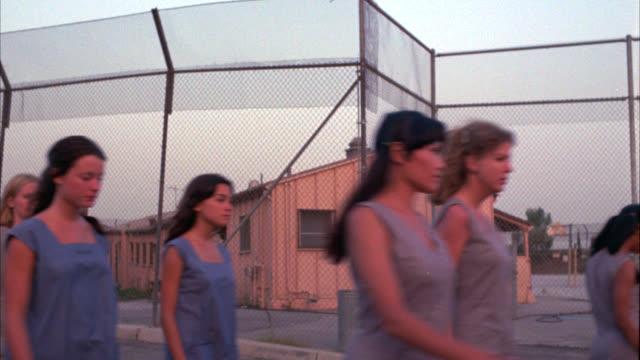 pan left to right of women inmates, prisoners walking through a prison yard. - women prison stock videos & royalty-free footage
