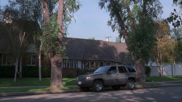 wide angle of a jeep cherokee parked on street in front of one story, middle class house in a residential area, neighborhood or the suburbs. trees and lawn in front yard. - vierradantrieb stock-videos und b-roll-filmmaterial