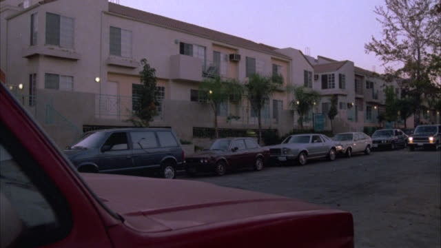 wide angle of a middle class, two story stucco apartment building, condominium or townhouse with red tile roof. cars parked in front of building. red bronco also parked in fg. matching nx 1319-g. - 1987 bildbanksvideor och videomaterial från bakom kulisserna