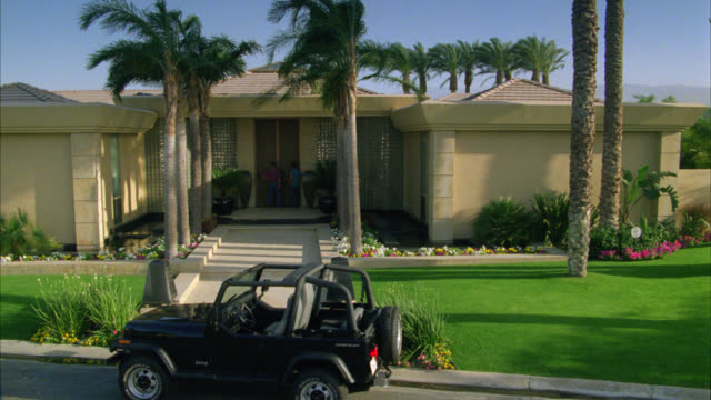 wide angle of two men standing outside front door of one story, upper class house in residential area or neighborhood. palm trees line the walkway in front of house. a cherokee jeep parked out front of house. - palm springs california stock videos & royalty-free footage