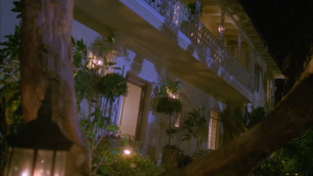 medium angle of two story, upper class house or mansion with trees and plants in front of house blowing in the wind. interior and exterior lights are on. - herrenhaus stock-videos und b-roll-filmmaterial