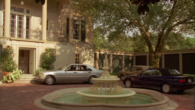 wide angle of a mercedes, saab and bmw parked in circular brick driveway in front of entrance to two story, upper class house, estate or mansion with water fountain in front. - zweistöckiges wohnhaus stock-videos und b-roll-filmmaterial