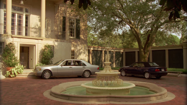 wide angle of a mercedes and bmw parked in circular brick driveway in front of entrance to two story, upper class house, estate or mansion with water fountain in front. - zweistöckiges wohnhaus stock-videos und b-roll-filmmaterial