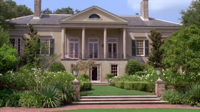 wide angle of a two story, upper class house, mansion or estate with columns and a balcony. well manicured lawn and garden with brick walkway in fg. - stately home stock videos & royalty-free footage