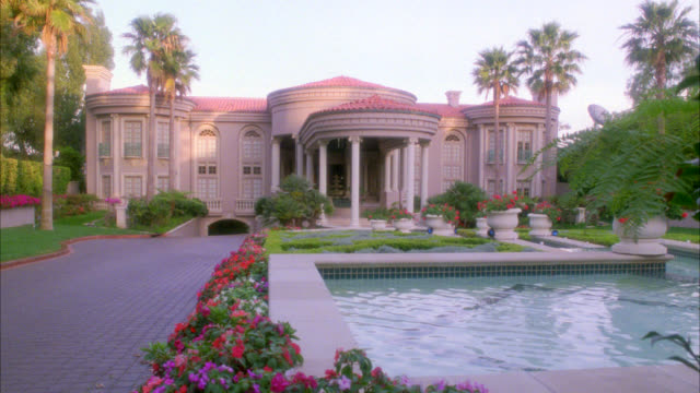 wide angle of two story, upper class, spanish style estate, mansion or house with red tile roof with fountain or pool of water and plants, flowers next to driveway in fg. palm trees. matching match nx is 1441-a  another dx is 1439-e 1441-d expensive - fountain stock videos & royalty-free footage