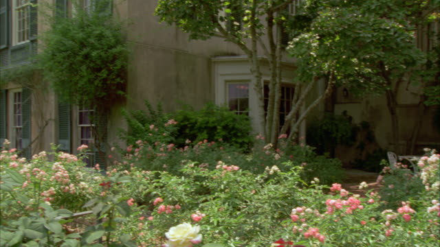pan right to left of upper class, two story southern-style house or mansion with tall windows,  shutters, columns. large backyard includes rose garden, trees. could be used as villa.  around cameo has matching nx on reel 4059 - zweistöckiges wohnhaus stock-videos und b-roll-filmmaterial