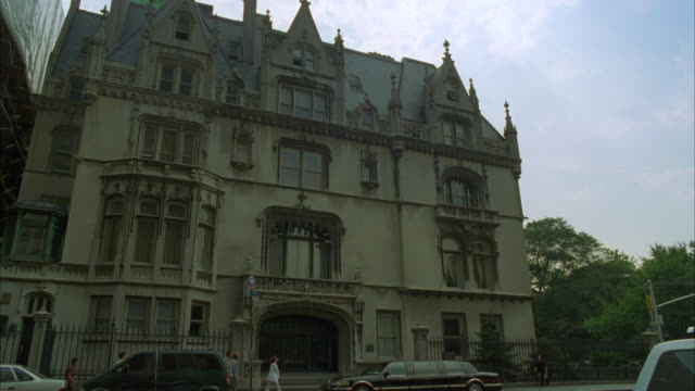 wide angle of four story, ornate stone building with gothic architecture surrounded by a rod iron fence. could be convent, mansion, historical society. cars drive by in fg. building is ukrainian institute of america on 79th street and fifth avenue. match - convent stock videos & royalty-free footage