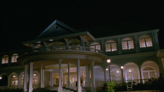 WIDE ANGLE OF TWO STORY, UPPER CLASS MANSION, ESTATE OR RESORT WITH CIRCULAR BALCONY AND MAN STANDING AT ENTRANCE TO DOOR. INTERIOR AND EXTERIOR LIGHTS ON.