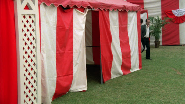 wide angle of red and white striped tent. could be at circus, fair or carnival. [shots 1219-06 thru 1219-10 match]. - circus stock videos & royalty-free footage