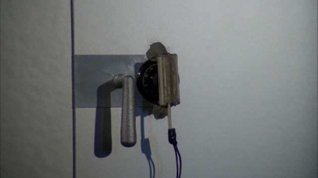 close angle of safe with c4 plastic explosive on dial. handle of safe blown open. flying debris. explosions. could be during robbery or heist. - esplosivo video stock e b–roll