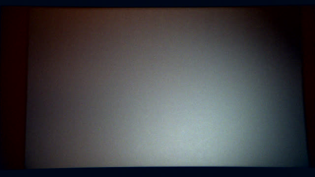 wide angle of movie projection screen. white light flickers, hits screen. for burn in. could be in movie theater. - projection screen stock videos & royalty-free footage