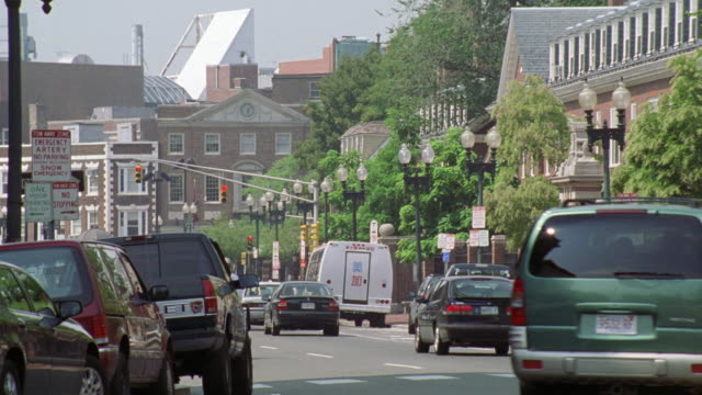 wide angle of harvard square in boston. cars, trucks, and vans on city street. brick buildings and high rises in bg. new england. - 2000 stock videos & royalty-free footage