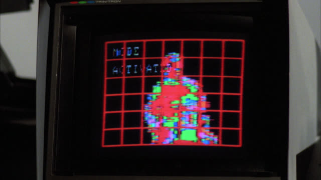 close angle of television video monitor screen. computer graphics on display of graph matrix with video under. heat sensor patterns or heat video in shape of person in chair or cockpit. could  be military or surveillance footage. could be video games or s - war stock-videos und b-roll-filmmaterial