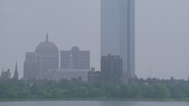 pan up from charles river  to boston skyline. trees in fg. skyscrapers, high rises, and apartment or office buildings. neg cut. longfellow bridge over boston harbor with city skyline in bg. - longfellow bridge stock videos and b-roll footage