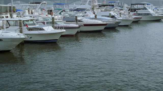 wide angle of boston harbor with pleasure boats anchored in marina. charles river.. longfellow bridge in bg. arch bridge. city skyline behind bridge. - longfellow bridge stock videos and b-roll footage