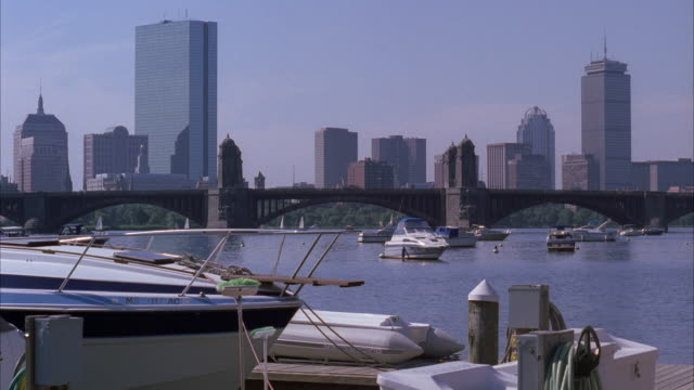 wide angle of boston city skyline with high rises and skyscrapers. marina or harbor with boats. longfellow bridge visible in bg. cities. boston harbor. skyscrapers and high rises visible. buoys visible. - longfellow bridge stock videos and b-roll footage