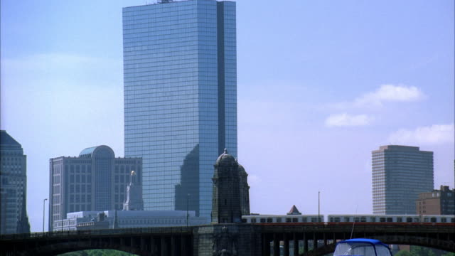 medium angle of longfellow bridge in boston. metro or commuter train passes across bridge from right to left. top of boat visible in boston harbor. city skyline in bg. skyscrapers and high rises. could be office buildings. - longfellow bridge stock videos and b-roll footage