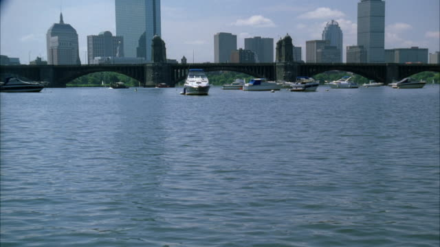 pan up from boston harbor and charles river to boston city skyline. boats and yachts in harbor. high rises and skyscrapers. longfellow bridge. neg cut. boats in harbor. - river charles stock videos & royalty-free footage