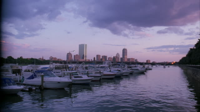 wide angle of marina in boston harbor. charles river. boats anchored at docks. sunset. boston city skyline in bg. high rises and skyscrapers. - river charles stock videos & royalty-free footage
