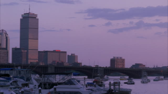 pan right to left across marina in boston harbor. charles river. boats anchored at docks. sunset. boston city skyline in bg. high rises and skyscrapers. longfellow bridge in bg. - river charles stock videos & royalty-free footage
