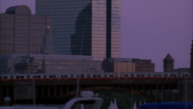 pan left to right as train moves across longfellow bridge in boston. boston city skyline with high rises and skyscrapers in bg. john hancock tower visible. - longfellow bridge stock videos and b-roll footage