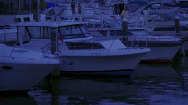 pan up from boats docked in marina in boston harbor to city skyline. john hancock tower. high rises and skyscrapers. longfellow bridge in bg. - longfellow bridge stock videos and b-roll footage