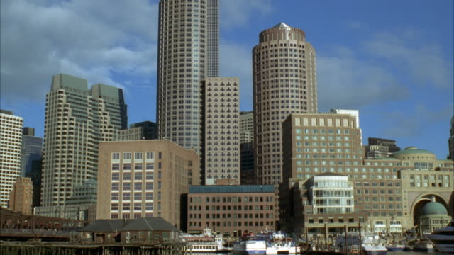 wide angle of downtown boston skyline. boston harbor and charles river in fg. high rises, sky scrapers, and office buildings. - river charles stock videos & royalty-free footage
