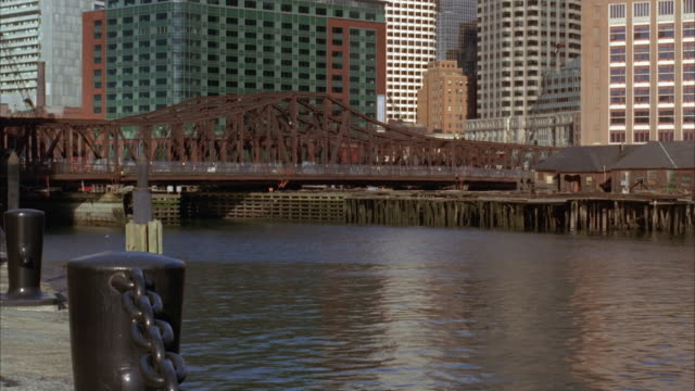 wide angle of steel bridge spanning water in boston harbor. traffic moving over old north ave. bridge. charles river in fg. office buildings visible in bg. - チャールズ川点の映像素材/bロール