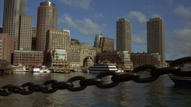 pan right to left of boston harbor as ferry moves towards docks. charles river. high rises, skyscrapers, and office buildings. boston city skylines. black chain in fg. - river charles stock videos & royalty-free footage