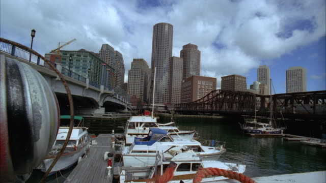wide angle of boston harbor and marina. old north ave. bridge in bg. spinning roof vent in fg. high rises and downtown boston skyline in bg. boats anchored in marina. docks. - マリーナ点の映像素材/bロール