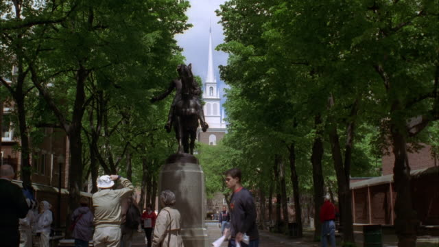 wide angle of paul revere mall with statue of paul revere on horse. old north church in bg. north end of boston. tourists visible. - old north church stock videos & royalty-free footage